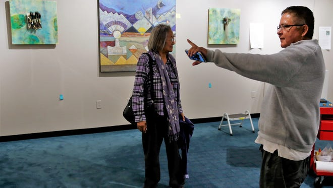 "Artists Gloria Emerson and Michael Billie check on preparations for the opening of their ""Color Me Opinionated"" exhibition on Thursday at the Henderson Fine Arts Center Art Gallery at San Juan College."