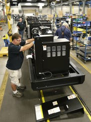 Workers at Generac Power Systems assemble a generator