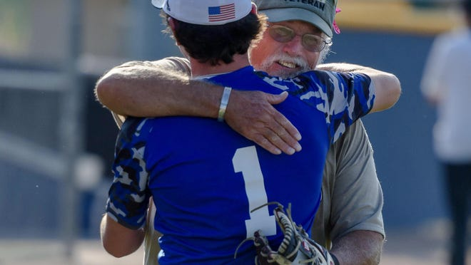 United States veteran Robert Williamson hugs his grandson Kellen Williamson (1), a senior on the Battle baseball team, before throwing out a ceremonial first pitch Tuesday during a military appreciation night at Atkins Sports Complex.