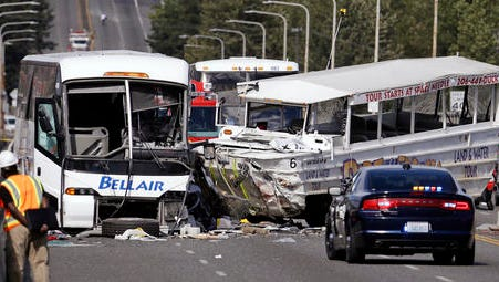 "FILE - In this Sept. 24, 2015, file photo, a ""Ride the Ducks"" amphibious tour bus, right, and a charter bus remain at the scene of a fatal collision on the Aurora Bridge in Seattle. The National Transportation Safety Board meets Tuesday, Nov. 15, 2016, to determine the probable cause of the crash of the Ride the Ducks vehicle after it crossed the center line into oncoming traffic while driving over the bridge. It hit a charter bus full of college students, killing five. (AP Photo/Elaine Thompson, File)"