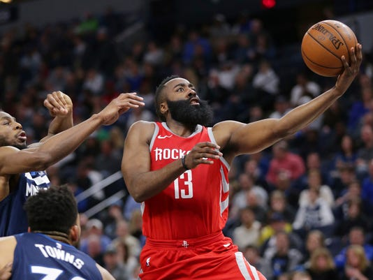Houston Rockets James Harden (13) shoots past the Minnesota Timberwolves' Andrew Wiggins (22) and Karl-Anthony Towns in the fourth quarter of an NBA basketball game Sunday, March 18, 2018, in Minneapolis. The Rockets defeated the Timberwolves 129-120. (AP Photo/Andy Clayton-King)