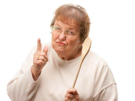 Upset Senior Woman with The Wooden Spoon Isolated on a White Background.