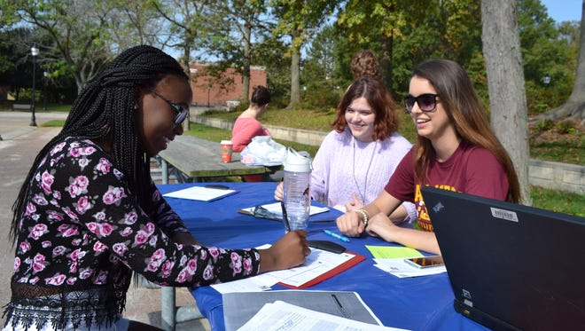 Tendo Nassozi, left, a freshman at Salisbury University from Montgomery County, fills out a request for an absentee ballot. Kitty Felbinger, center, and Ellie Brookbank, members of the SU chapter of College Democrats, helped with the drive on campus on Thursday, Oct. 20, 2016.