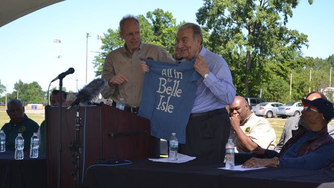 Ed Deeb receives a T-shirt from Ron Olson, Department of Natural Resources parks and recreation chief, on Friday during a ceremony in which a street on Belle Isle was named for Deeb.