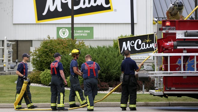 Members of the Grand Chute Fire Department collect one of their hoses after a call to McCain Foods USA Tuesday in Grand Chute.