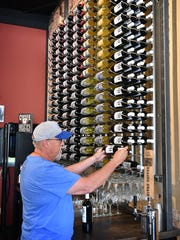 Hook & Ladder Coffees & Winery co-owner Bill Weske stocks the massive wine rack that holds more than 500 bottles of wine. The new business opens Friday offering artisan roasted coffees and an urban winery