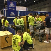 Mystery Machine team members from Eden Valley-Watkins Secondary School work on their robot in the pit area during the FIRST Robotics Competition world championships in St. Louis.