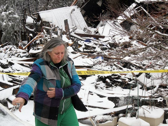 Claire Jones walks past the rubble of her home Tuesday morning, February 17, 2015. The blaze at 182 Pinehurst Drive in Brick Township late Monday night consumed the home. WITH VIDEO BRICKFIRE0217A BRICK TOWNSHIP, NJ STAFF PHOTO BY THOMAS P. COSTELLO