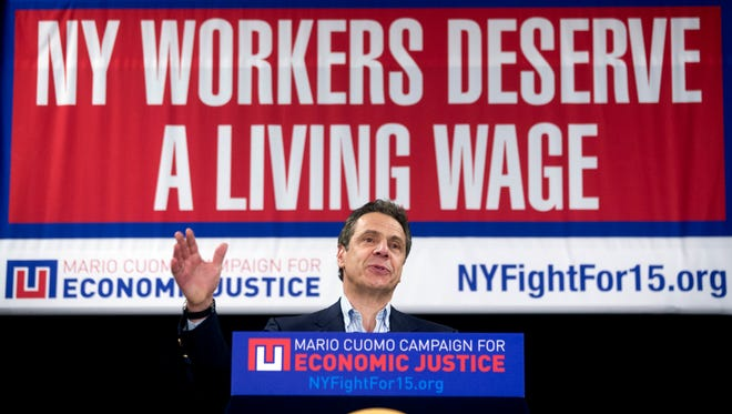 In this Feb. 25, 2016, file photo, New York Gov. Andrew Cuomo speaks during a rally to raise the minimum wage in Albany, N.Y. A federal court on Tuesday, Nov. 22, 2016, blocked implementation of a rule imposed by President Barack Obama's administration that would have made an estimated 4 million more higher-earning workers across the country eligible for overtime pay starting Dec. 1. The U.S. District Court in the Eastern District of Texas granted the nationwide preliminary injunction that prevents the Department of Labor from implementing the changes while the regulation's legality is examined in more detail by the court.