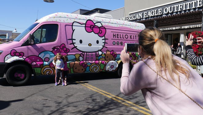 Flavia Testa takes a photo of her daughter Victoria and her friend Bianca in front of the Hello Kitty Cafe Truck in Gilbert, Ariz. on Feb. 24, 2018.
