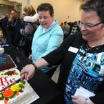 Sheri Folta, left, and her wife, Cassandra Varner, slice one of two anniversary cakes together last month in Ferndale, Mich.