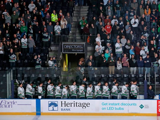 Seattle Thunderbirds hockey players join fans in standing