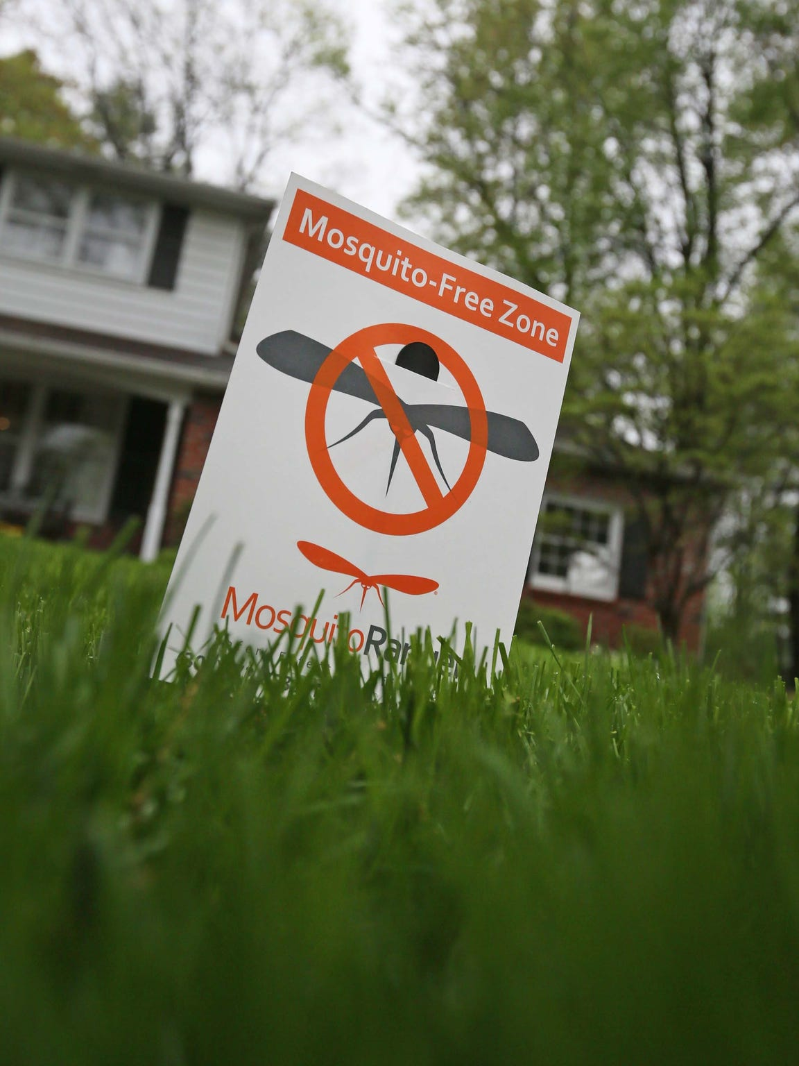 A sign saying a lawn has been treated for mosquitoes is shown on a North Wilmington lawn.