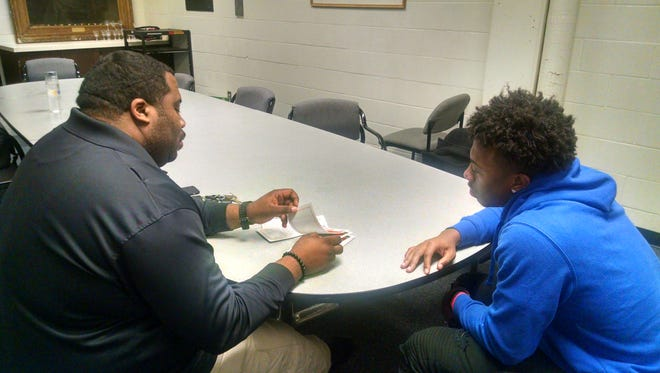 In this Jan. 19, 2018, photo, North High School football coach Charles Adams, left, and football team member Nasir El-Amin go over questions from the Coaching Boys Men Training Program at North High School in Minneapolis. (Mike Moen/Minnesota Public Radio via AP)