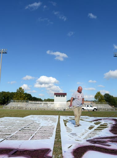 C. Ray Pruitt, center, and Todd Wessells paint a warrior head on the 50-yard line prior to Nandua's homecoming game on Friday, Oct. 17, 2014 in Onley, Va. Pruitt volunteers with the team as a medic during games and paints the field before home games.
