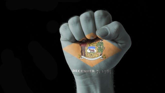 A fist painted in colors of Delaware's flag.