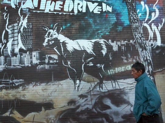 """A man walks past a mural with the words """"At The Drive"""