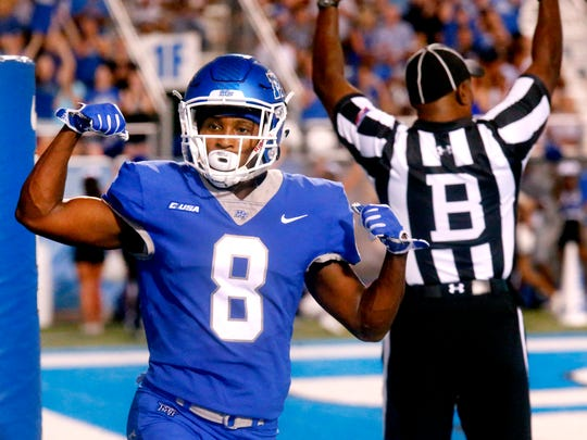 MTSU's Ty Lee (8) celebrates his touchdown as the official indicates the touchdown against Bowling Green in the background during the game on Saturday, Sept. 23, 2017.