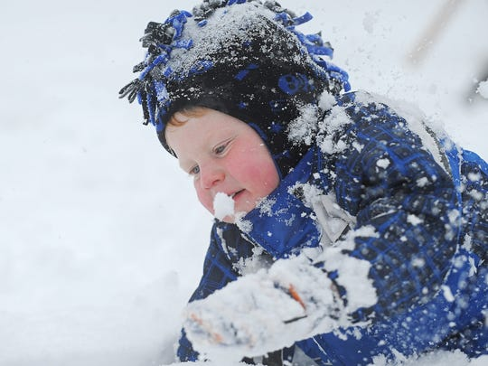 Bridger Wagner, 3, of Sioux Falls, plays in the snow outside his house during the first snow of the season Friday, Nov. 20, 2015, in Sioux Falls.