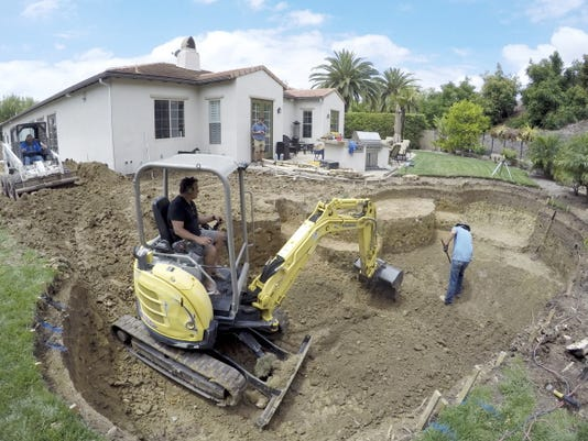 In this photo taken on Wednesday, May 20, 2015, a construction crew digs a new pool behind a house in Tustin, Calif. As residents struggle to reduce potable water consumption by 25 percent, the California Pool and Spa Association is promoting a campaign called Letís Pool Together and aggressively lobbying water districts to quash proposed bans on filling pools and spas.