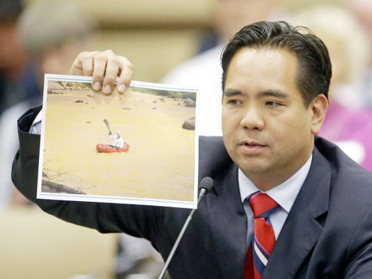 Utah Attorney General Sean Reyes holds a photograph from the massive spill from the abandoned Colorado gold mine that sent toxic wastewater flowing into Utah and at least two other states during the State Water Development Commission meeting Tuesday, Aug. 18,  2015, in Salt Lake City. Reyes told Utah lawmakers that he first wants to see how the Environmental Protection Agency proposes to fix the damage to the state's waters, but legal action will be on the table if their actions fall short. (AP Photo/Rick Bowmer)