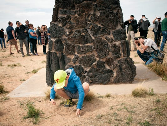 8-year-old Josiah Fidel, of Albuquerque, plays in the dirt next to the obelisk commemorating the first atomic bomb test at the Trinity Site as other visitors to the site take photographs. The White Sands Missile Range opened the Trinity Site to the public for an open house commemorating the 70th anniversary of the first atomic test which took place there on July 16th, 1945. Several thousand visitors came to see the site, take photographs and learn more about the event. While the mood at the site seemed celebratory, at the Missile Range's two entrances leading to the site small groups of protestors gathered to raise awareness of the health impact of the test which they say has lead to a marked increase of cancer in the communities that bordered the Trinity area.