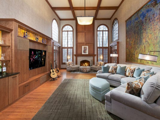 """A large """"conversation"""" sofa was placed against the wall in this narrow room, allowing those seated to talk with one another, view the television and face the fireplace area?, as well."""