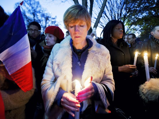 Alexandra Salomon, from Paris, France, joins a vigil outside the White House in Washington, Saturday, Nov. 14, 2015, to pay tribute to the victims of the Paris attacks. Multiple attacks across Paris on Friday night have left scores dead and hundreds injured. (AP Photo/Manuel Balce Ceneta)