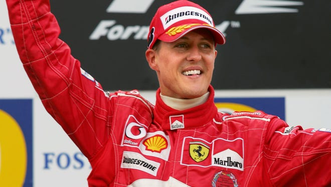 A photo taken on August 29, 2004 shows Ferrari's German driver Michael Schumacher holding his trophy on the podium of the Spa-Francorchamps racetrack after winning the Belgium Grand Prix, in Francorchamps, Belgium, and his fith consecutive driver's championship title, the seventh and final of his career. Michael Schumacher, the retired seven-time Formula One champion who often braved death on the tracks, remained in a critical condition on December 30, 2013 after an off-piste skiing accident in the French Alps. The German racing legend, who turns 45 at the end of the week, had been skiing off-piste on December 29, 2013 with his 14-year-old son in the upmarket Meribel resort when he fell and hit his head on a rock, prompting an urgent evacuation by helicopter.