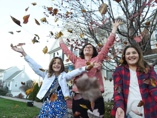 Lucille Grippo, 45, center, throws leaves up in the