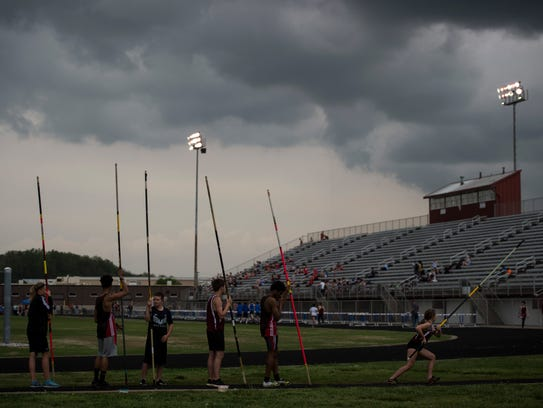 An ominous rain cloud hangs over the track as pole-vaulters