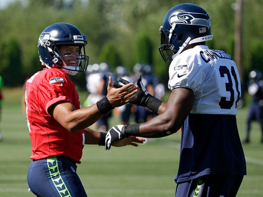 Seattle Seahawks quarterback Russell Wilson, left,