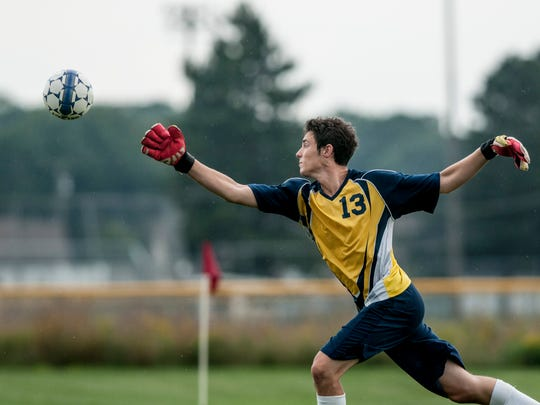 Capac's Jake Witt tries to deflect a shot during a