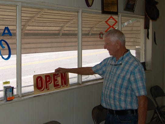 Barber Lonnie Ash flips his business sign from 'Open'
