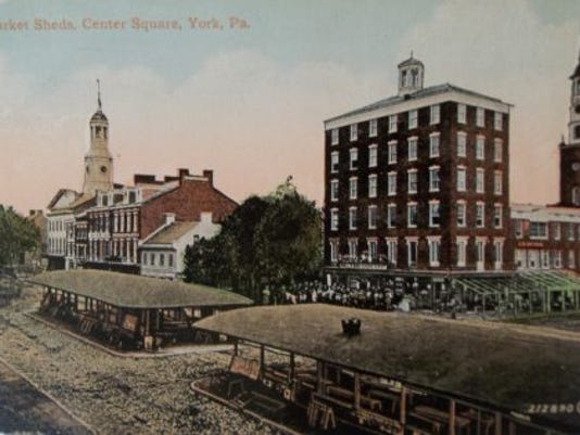 The steeple of Christ Lutheran Church (right) on S. George Street towers over the Hartman store at the corner intersection with Market Street in this colorized postcard of a Civil War-era photograph of the square and market sheds. Under the western market shed was a lock up where miscreants were incarcerated. (Author's postcard collection)