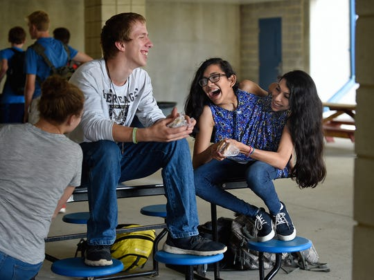 """Carmen and Lupita Andrade hang out with friend Joe Kimberly during a lunch period at Nonnewaug High School in Woodbury where they study agriscience. Kimberly, who grew up on a farm and also studies agriscience, has known the twins since kindergarten. """"They're no different than you or me,"""" Kimberly said. """"They're like two peas in a pod."""""""