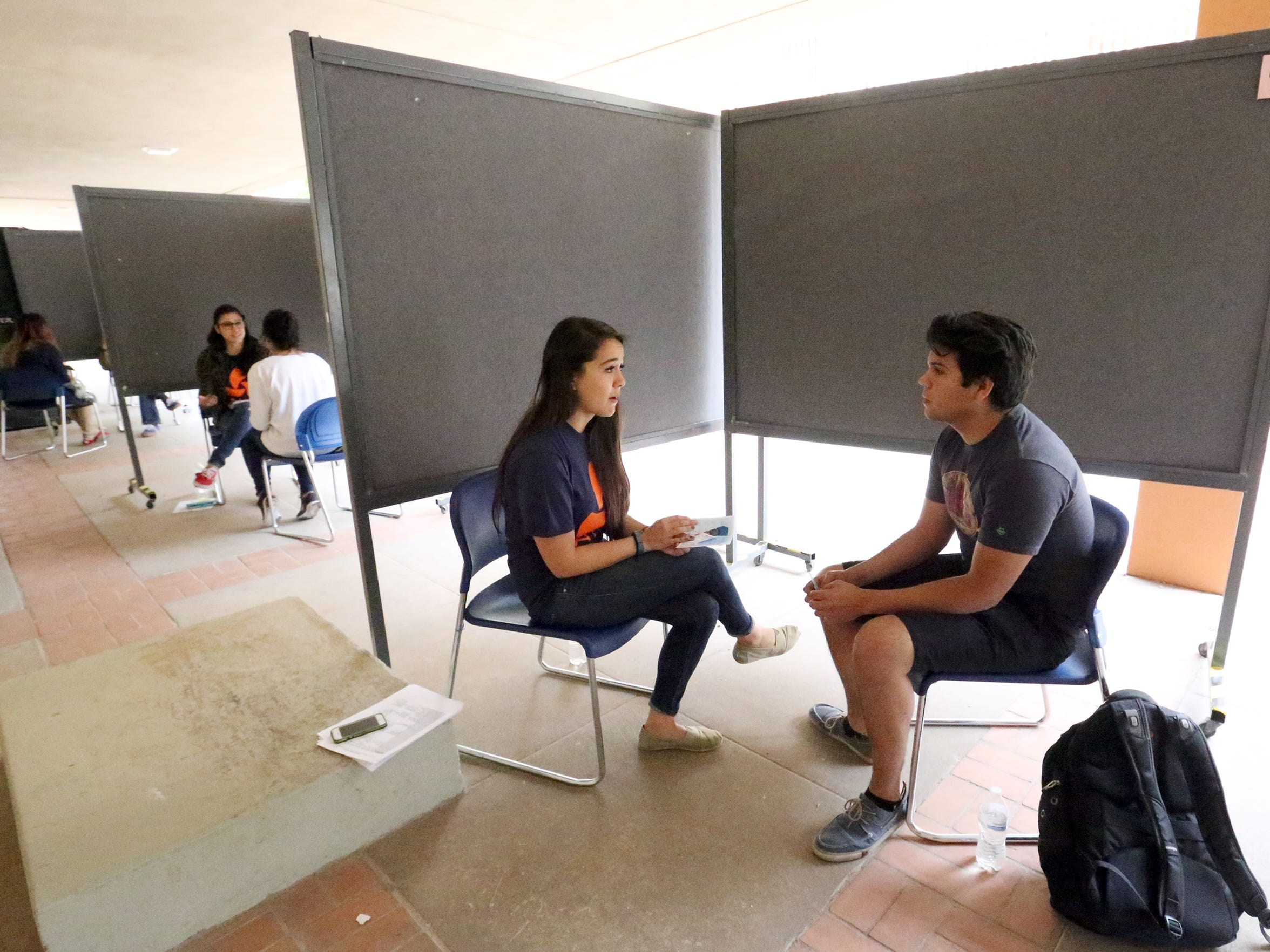 Clinical psychology student Reyna Puentes, left, interviews mechanical engineering student David Baca during a research initiative Thursday, April 7 at the UTEP student union courtyard. The research was conducted by the Latinos Alcohol Health Disparities Research Center at UTEP.