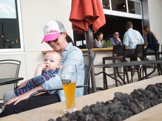 Ashley Branson and her daughter, Blake, 1, enjoy the sunshine on the patio at D.C. Oakes Brewhouse and Eatery on Tuesday, May 1, 2018.