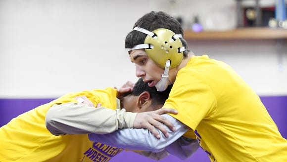 North Henderson's Josh Blatt, right, wrestles with