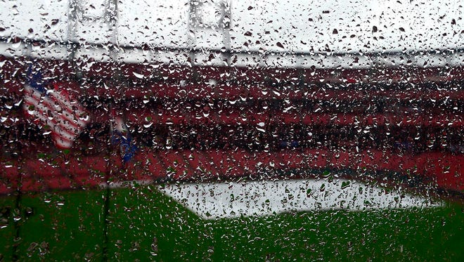 The tarp covers the field at Busch Stadium after the game between the St. Louis Cardinals and the Milwaukee Brewers was postponed Wednesday due to heavy rain.