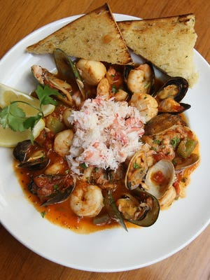 A bowl of Cioppino at Bluewater Grill in Phoenix.  Cioppino is traditionally made from the catch of the day, which in the dish's place of origin is typically a combination of dungeness crab, clams, shrimp, scallops, squid, mussels and fish with fresh tomatoes in a wine sauce.