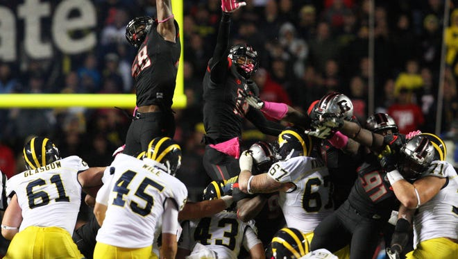 Mark R. Sullivan/Staff photographer Rutgers' Kemoko Turay (left) skies to block a Michigan field goal attempt in 2014.