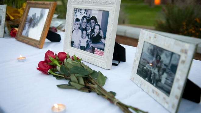 In this Oct. 2, 2014 file photo, flowers and photos are on display during a vigil for the Strack family at Pioneer Park in Provo, Utah.