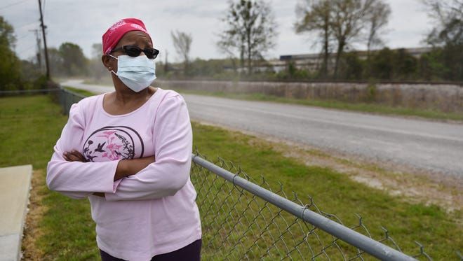 Her face masked to shield  pollen earlier this year, Belinda Kincaid looks over the road that separates her home in Grenada?s Eastern Heights subdivision from a manufacturing plant. that for years was the source of chemicals that now pollute the area groundwater.