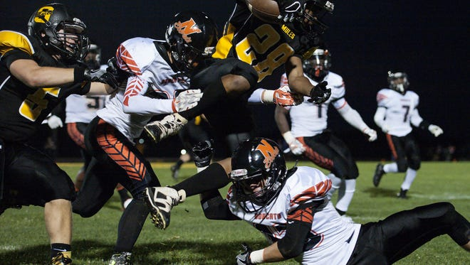 Northeastern's Blake Einsig (right) and Wyatt Hughes (left) take out Solanco running back Nafis Moore last season.