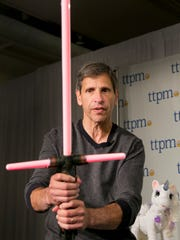 "In this Sept. 29, 2015, photo, Jim Silver, CEO of Toys, Tots, Pets & More, discusses the Star Wars The Black Series Kylo Ren Force FX Lightsaber at the TTPM Holiday Showcase in New York. The U.S. toy industry is expected to have its strongest year in over a decade, with anything ""Star Wars,"" robotic and life-like pets expected to drive holiday sales."