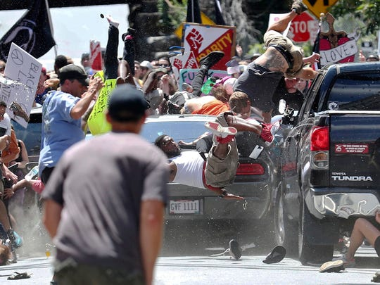 People fly into the air as a vehicle drives into a group of protesters demonstrating against a white nationalist rally in Charlottesville, Va.