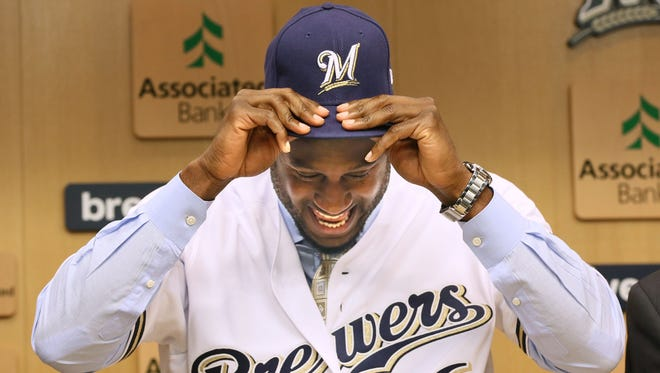 Lorenzo Cain dons a Brewers jerey and cap during a news conference following his signing last week.