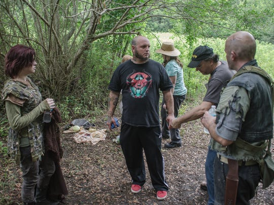 """Cast members Anna Faulkner, left, and Jason Robbins, right, discuss a scene with visual effects artist Lemmie Crews and director Stephen Wise on the set of """"Sur'vi."""""""