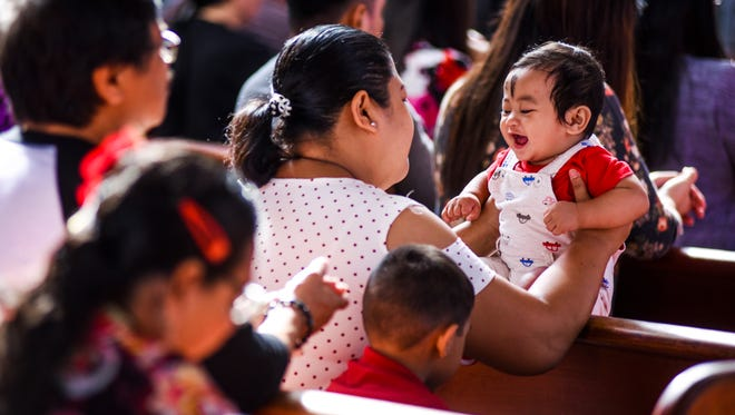 With his forehead annoited with ash, nine-month-old Jayvee Quenadas attends an Ash Wednesday Mass with his mother, Amelyn Quenadas, and other parishioners at the Dulce Nombre de Maria Cathedral Basilica in Hagåtña on Feb. 14, 2018.